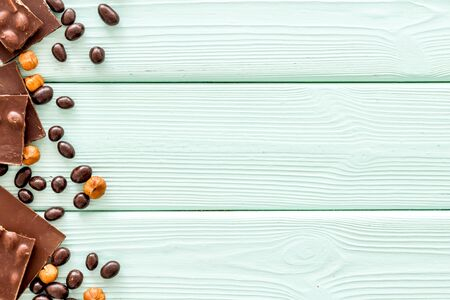 Chocolate with nuts and its ingredients on mint green wooden background top view copyspace