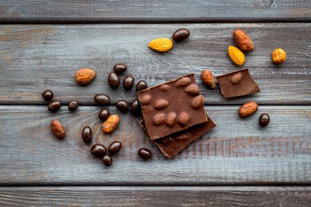 Different variety of chocolate and hazelnut on wooden background top view