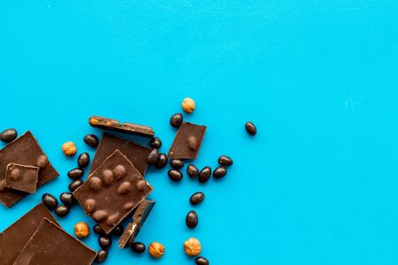 Different variety of chocolate and hazelnut on blue background top view space for text