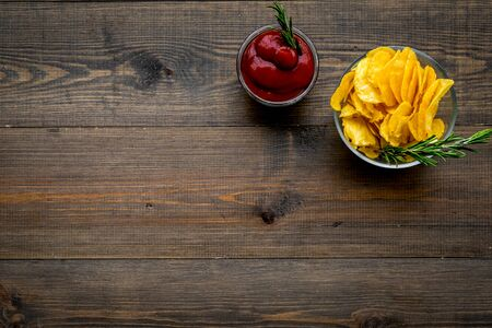 Junk food concept with heap of potato crisps and tomato sauce on wooden background top view space for text