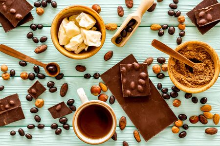 Cook homemade chocolate with bars, nuts, coffee beans on mint green wooden background top view