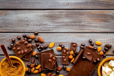 Chocolate bars and nuts on wooden table background top view mockup
