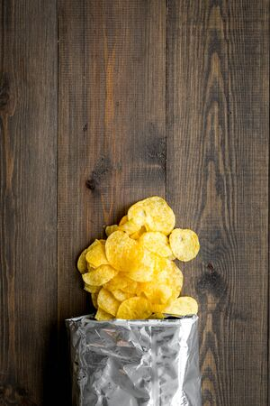 Junk food concept with potato crisps in bag on wooden background top view space for text Stockfoto