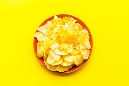 Potato chips in bowl ready to eat on yellow background top view Stockfoto