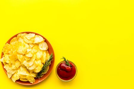 Potato chips served wiith ketchup on yellow background top view mock up