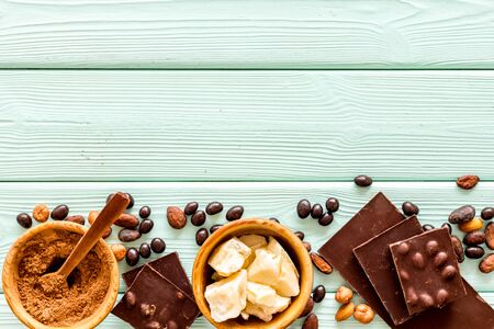 Cook homemade chocolate with bars, nuts, coffee beans on mint green wooden background top view mock up