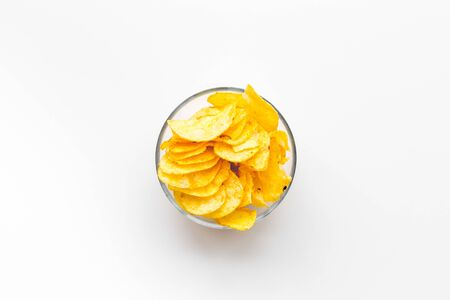 Bowl of homemade potato chips for snack on white background top view