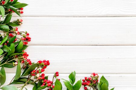Summer pattern with green plants and red berries on white wooden background top view mockup