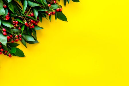 Summer pattern with green plants and red berries on yellow background top view mockup