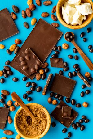 Chocolate with nuts and its ingredients on blue background top view