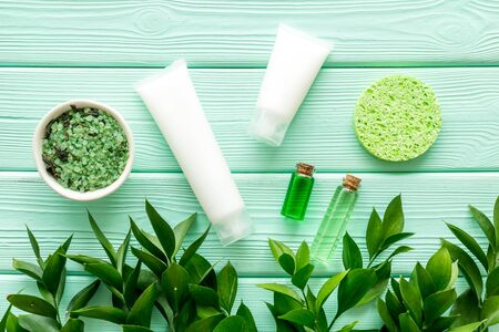 Cosmetics for face with cream from herbs on mint green wooden background top view Archivio Fotografico - 129423764