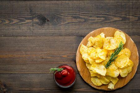 Papas fritas servidas con salsa de tomate en la vista superior de fondo de madera maqueta