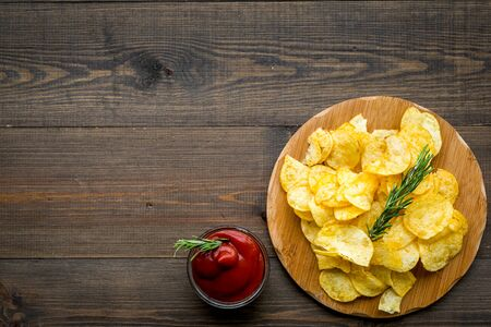 Potato chips served wiith ketchup on wooden background top view mock up