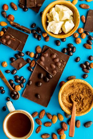 Cook homemade chocolate with bars, nuts, coffee beans on blue background top view Zdjęcie Seryjne