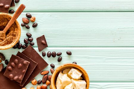 Different variety of chocolate and hazelnut on mint green wooden background top view space for text