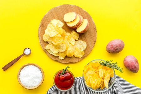 Fresh potato, tomato sauce, salt for cooking potato crisps on yellow background top view