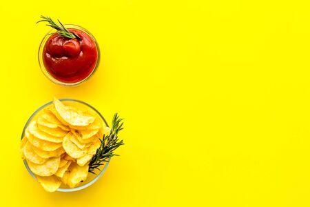 Potato crisps with tomato sauce on yellow background top view mockup