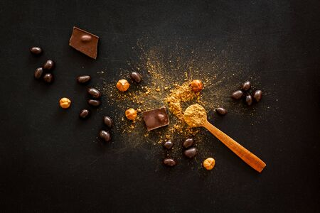 Cook homemade chocolate with bars, nuts, coffee beans on black background top view