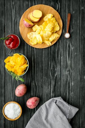 Potato chips served with ketchup and salt on wooden background top view