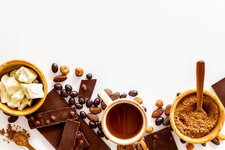 Different variety of chocolate with nuts and its ingredients. Cocoa beans, powder, hazelnut, bars on white background top view copyspace