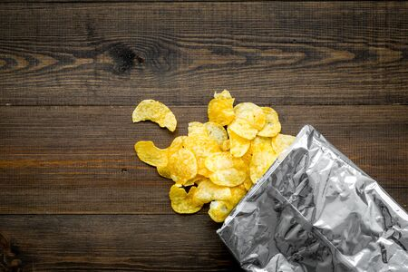 Junk food. Potato chips bag ready to eat on wooden background top view mock up Stockfoto