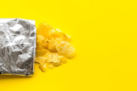 Fastfood. Bag of homemade potato chips for snack on yellow background top view copyspace