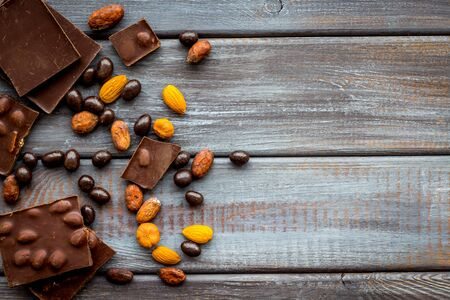 Homemade sweets. Chocolate bars and nuts on wooden table background top view mockup