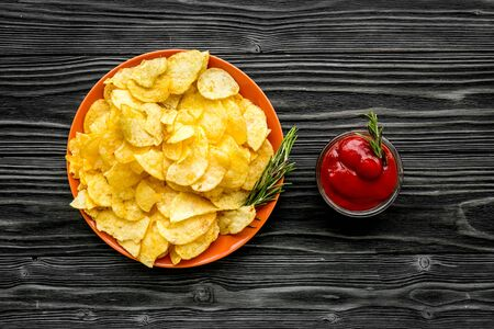 Fastfood. Homemade potato chips with ketchup for snack on wooden background top view Stockfoto