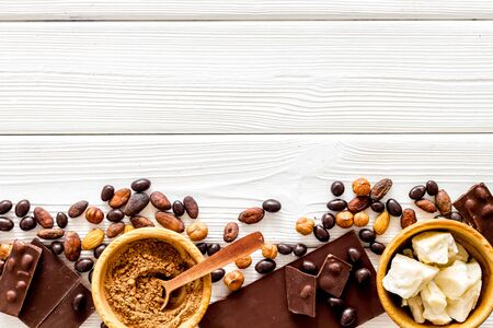 Homemade sweets. Chocolate bars and nuts on white wooden table background top view mockup