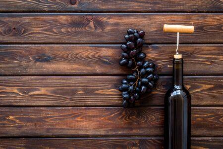 Testing wine concept. Wine bottle near black grape