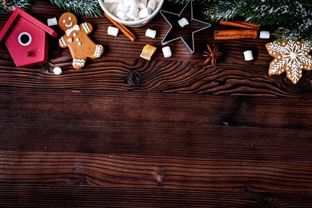 Christmas gingerbread, spruce branches on dark wooden background top view Stockfoto