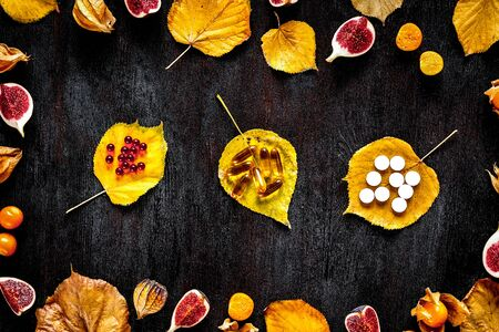 autumn leaves and sliced fruit on wooden background top view