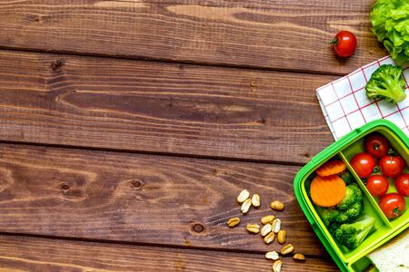 green lunch box for kid on wooden background top view