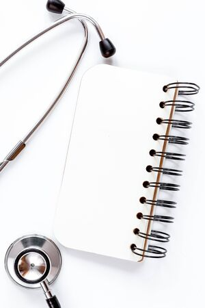 Entry to doctor blank open notebook with stethoscope top view