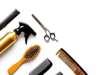 Peines y herramientas de peluquería sobre fondo blanco vista superior