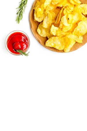 Junk food concept with heap of potato crisps and tomato sauce on white background top view space for text
