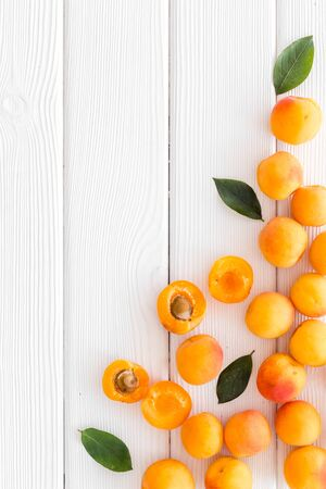 Fruit frame. Apricots and leaves on white wooden background top view copy space