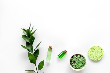 Cosmetics for face with sponge, salt, lotion from herbs on white background top view copy-space Imagens