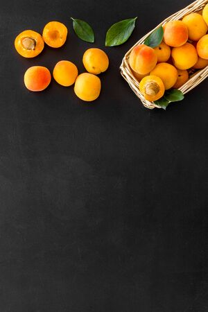 Collect apricots, black background top view space for text, pattern with leaves