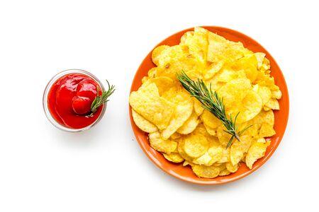 Potato crisps with tomato sauce on white background top view