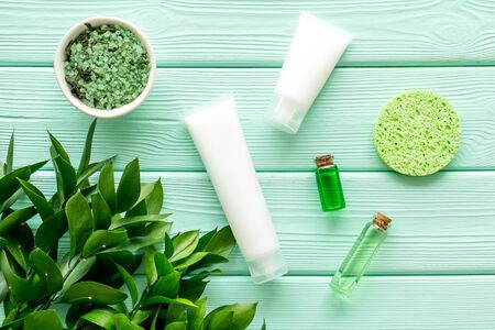 skin care with natural cosmetics with herbal extract on mint green wooden background top view