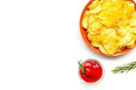 Potato chips served with ketchup on white background top view mock up