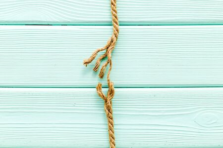risk concept with rope near to break on mint green wooden background top view space for text