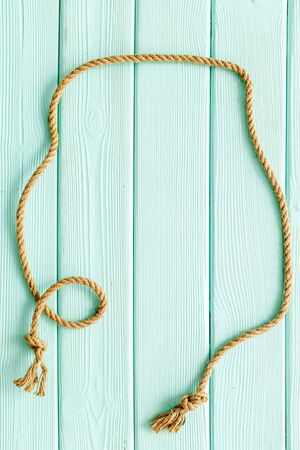 rope frame on mint green wooden background top view mock-up.