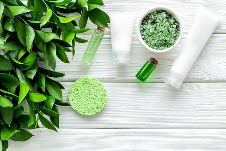 Organic cosmetics for face with cream, salt, lotion from herbs on white wooden background top view Imagens