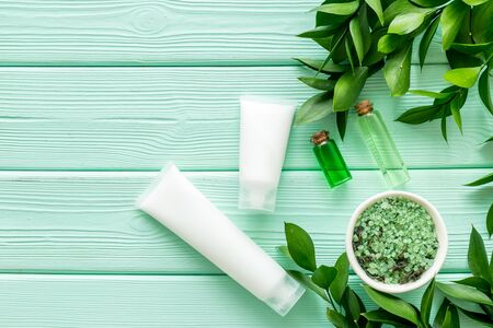 Cream, salt, lotion. Natural organic cosmetic set with green herbs on mint green wooden background top view mock up