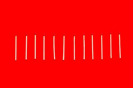 Symbol of danger with matches on red background top view.