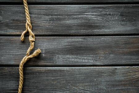 risk concept with rope near to break on wooden background top view space for text.