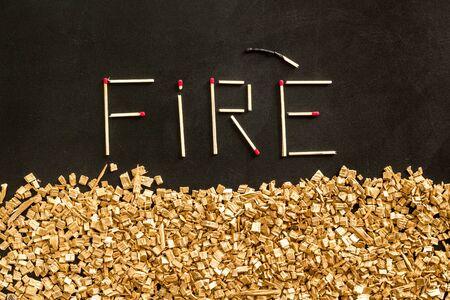 Simbolo del fuoco nei boschi con parola di fuoco da fiammiferi e cornice di accensione su sfondo nero vista dall'alto Archivio Fotografico
