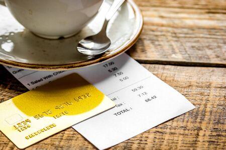 Restaurantrechnung, Kreditkarte und Kaffee auf Holztischhintergrund